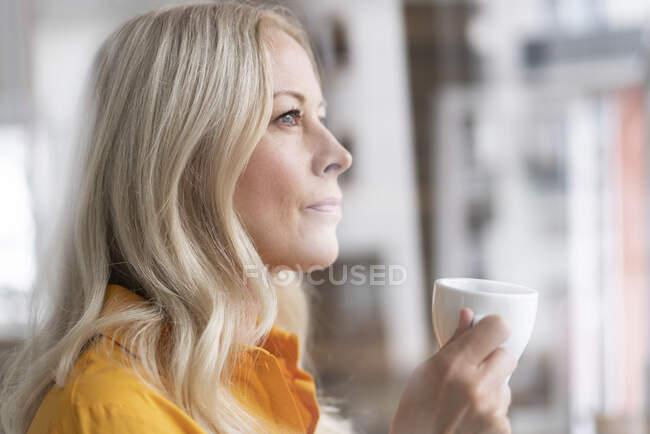Close-up de empresária pensativa segurando xícara de café em casa escritório visto através da janela — Fotografia de Stock