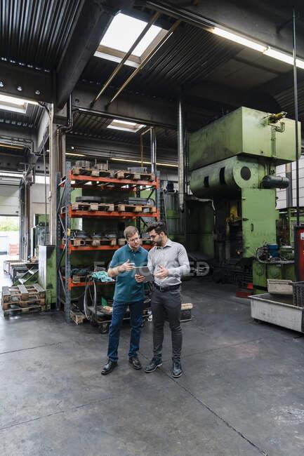 Colegas masculinos usando tablet digital em pé fábrica de fabricação — Fotografia de Stock