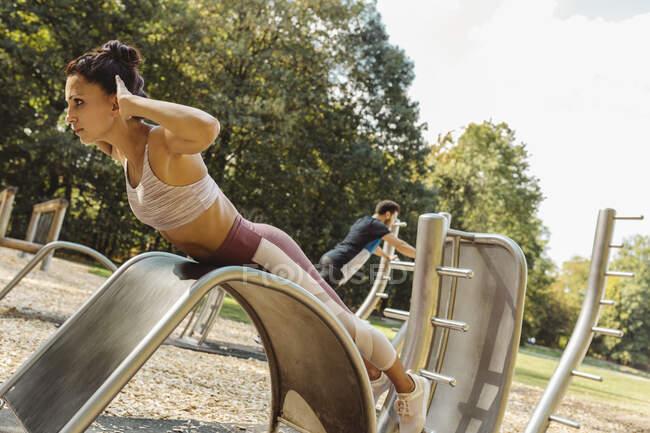 Mujer haciendo flexiones en un sendero de fitness - foto de stock