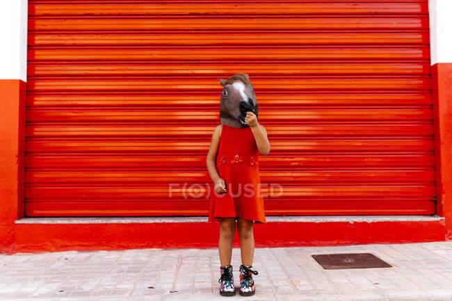 Niña con cabeza de caballo y vestido rojo delante del obturador rojo - foto de stock