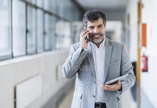 Щасливий професор чоловічої статі, який розмовляє по мобільному телефону, тримає цифрову табличку в коридорі в університеті — стокове фото