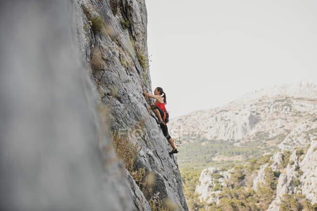 Scalatore di roccia femminile scalatore montagna contro cielo limpido — Foto stock