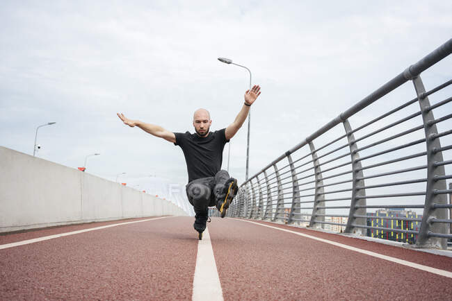 Young man performing stunt while inline skating on bridge against sky — стоковое фото