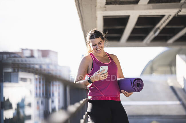 Smiling young woman holding exercise mat using smart phone while standing by railing - foto de stock