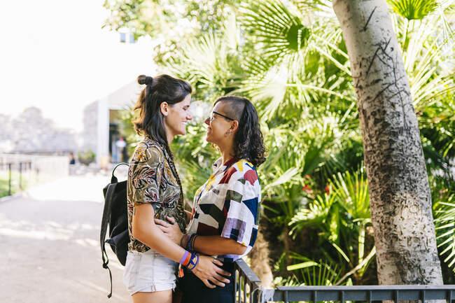 Affettuosa coppia lesbica guardando a vicenda in piedi all'aperto — Foto stock