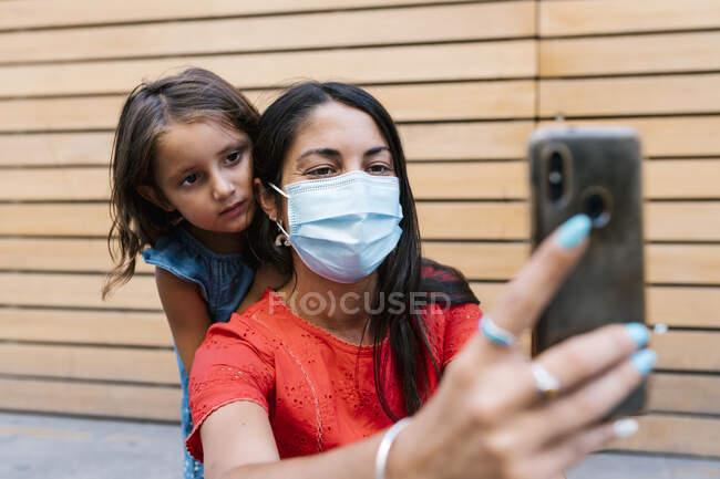 Madre usando máscara tomando selfie con hija contra la pared - foto de stock