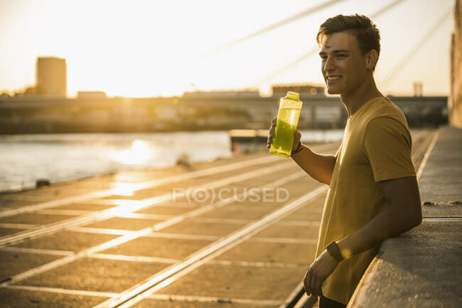 Man with water bottle after workout against clear sky — стоковое фото