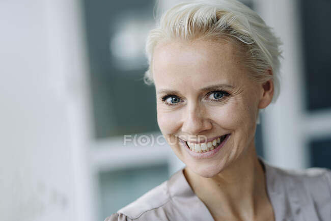 Close-up of cheerful businesswoman with short blond hair in office — Stock Photo