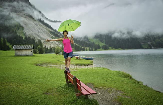 Playful woman holding umbrella while walking on bench at lakeshore against mountain range — Stock Photo