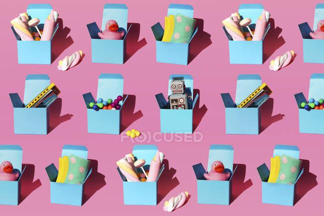 Патерн коробок з різними подарунками, включаючи губні гармонії, пластикові кулі, іграшки-вінтажні роботи, солодощі, качки-гуму і шкарпетки. — стокове фото