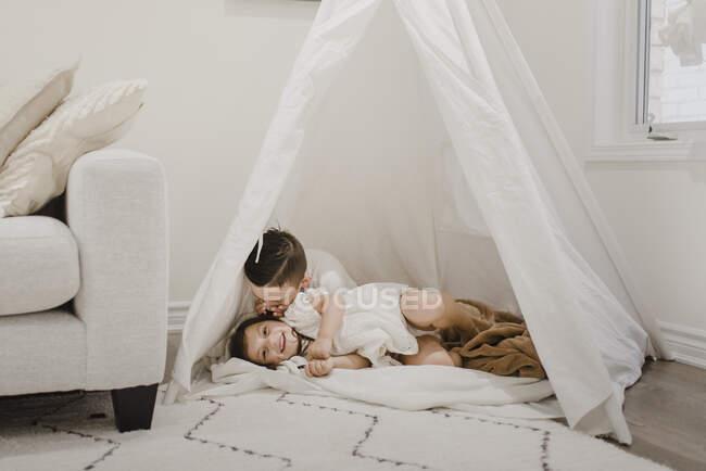 Irmão sussurrando no ouvido da irmã dentro da tenda na sala de estar — Fotografia de Stock
