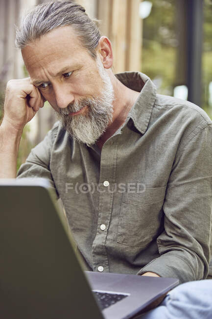 Close-up de homem maduro barbudo pensativo usando laptop enquanto sentado no quintal — Fotografia de Stock
