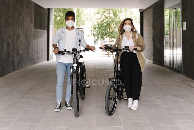 Пара в захисних масках стоїть з електричними велосипедами на стежці. — стокове фото