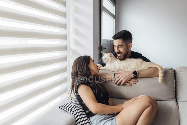 Пара дивиться на кота, сидячи на дивані. — стокове фото