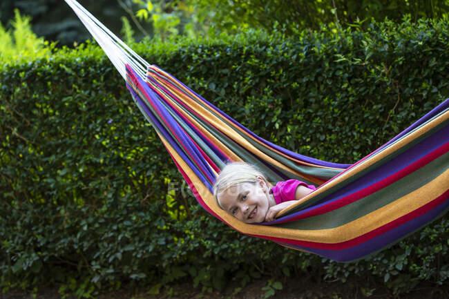 Chica sonriente relajándose en hamaca colorida en el jardín - foto de stock