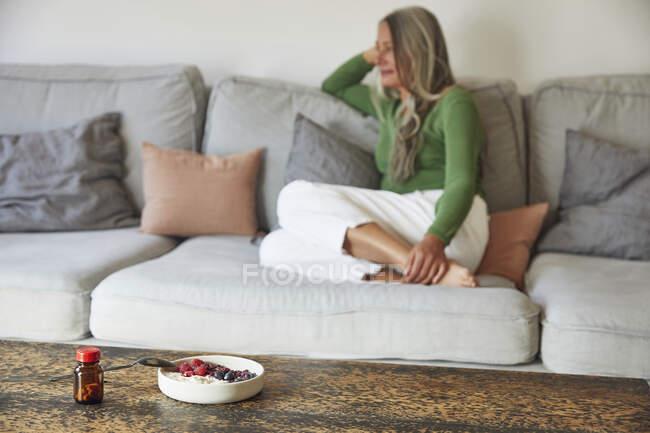 Доросла жінка сидить вдома на дивані. — стокове фото