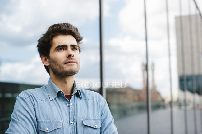 Close-up of thoughtful casual businessman looking away against modern building — Stock Photo