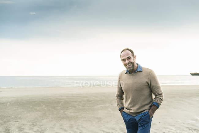 Glücklicher reifer Mann mit Händen in den Taschen, der lacht, während er gegen das Meer steht — Stockfoto