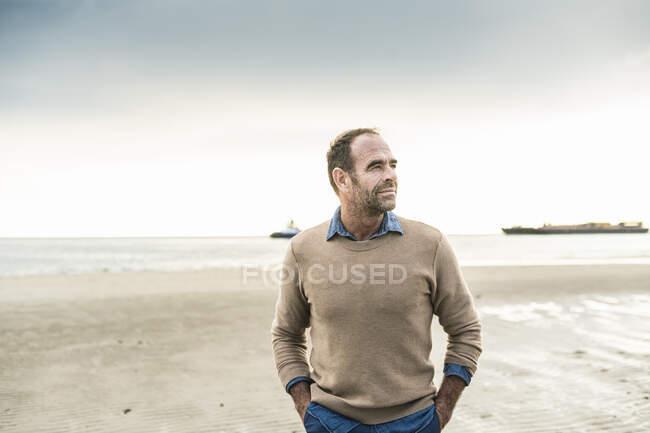 Reifer Mann mit den Händen in den Taschen, während er am Wochenende am Strand steht — Stockfoto