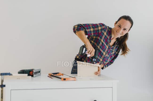 Smiling woman doing DIY work while standing against wall at home — Stock Photo