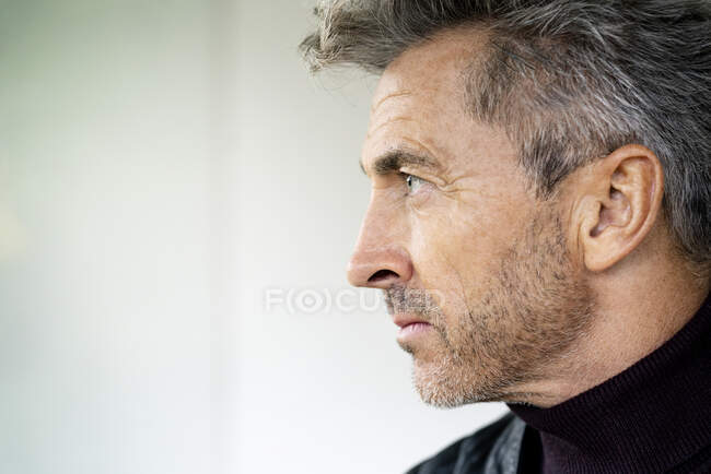 Close-up of serious thoughtful manager looking away against wall in office — Stock Photo