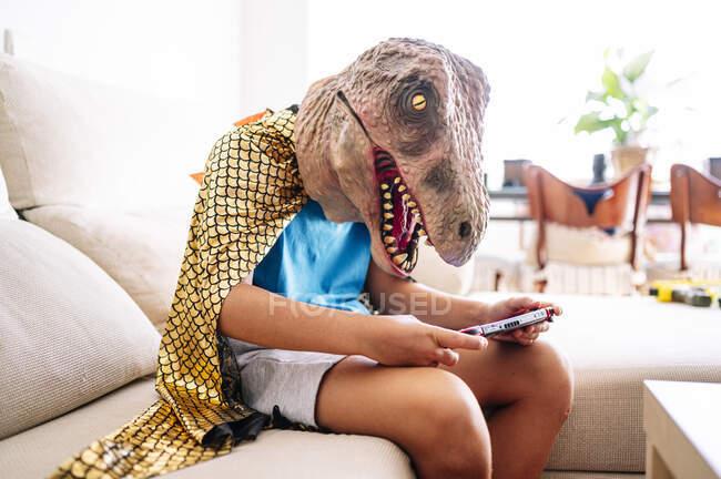 Ragazzo indossando maschera di dinosauro e mantello utilizzando smartphone mentre seduto sul divano a casa — Foto stock
