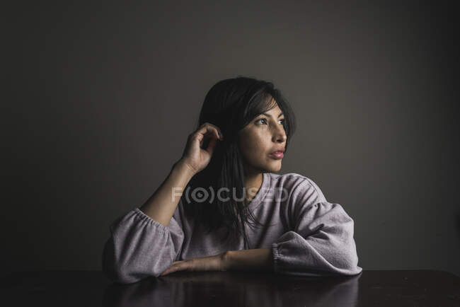 Thoughtful woman with black hair sitting at table against wall — Stock Photo
