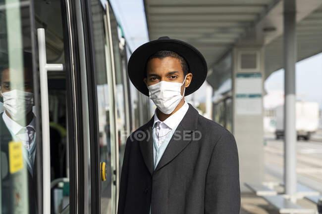 Jovem elegante em pé junto ao teleférico durante o COVID-19 — Fotografia de Stock