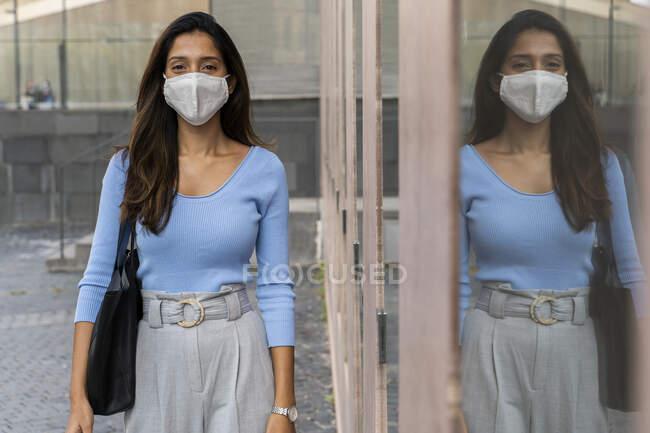 Joven empresaria con máscara protectora parada junto a una ventana de vidrio durante una pandemia - foto de stock