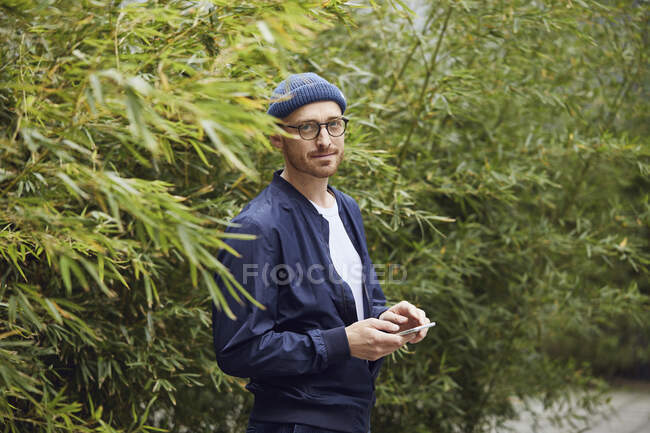 Man text messaging on smart phone while standing against green leaf in public park — Stock Photo