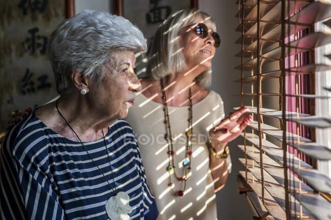 Mujeres amigas mayores mirando a través de persianas de ventana mientras están de pie en casa - foto de stock
