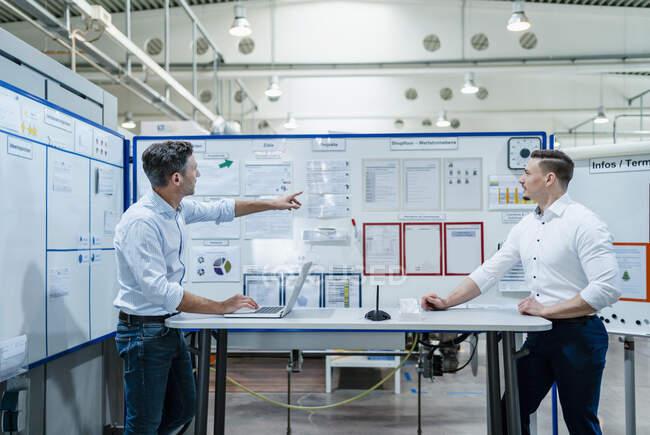Les gens d'affaires avec ordinateur portable ayant une réunion au bureau dans l'industrie — Photo de stock