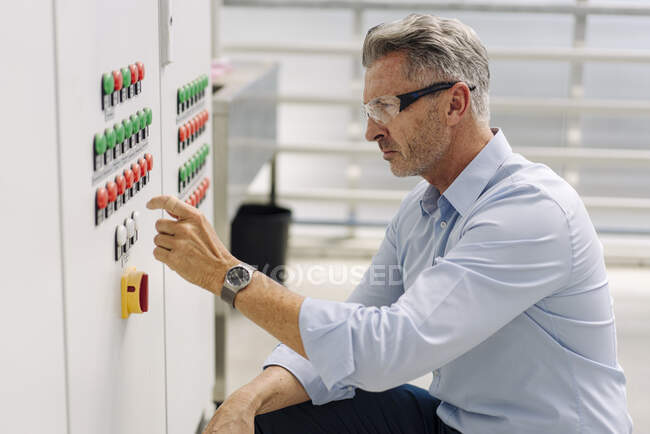 Businessman operating control panel while crouching in greenhouse — Stock Photo