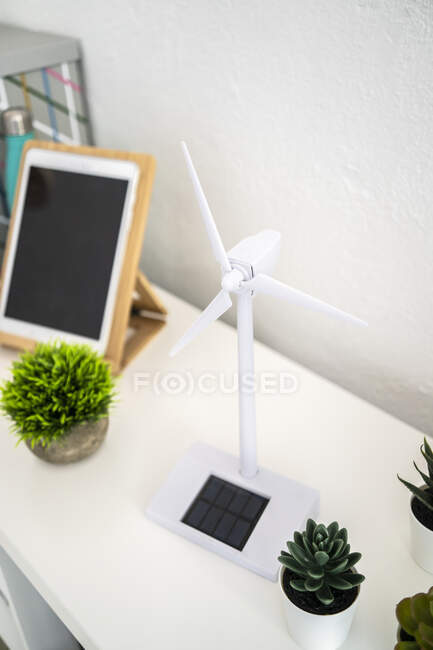 Small potted plants and wind turbine shaped electric fan — стоковое фото