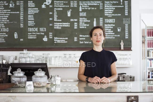 Довірлива жінка-власник стоїть біля стойки в кав'ярні. — стокове фото