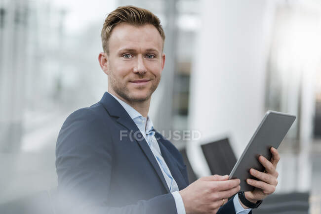 Confident businessman with digital tablet in city — Stock Photo