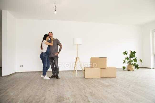 Романтическая пара, стоящая у электрической лампы и коробок, стоящих напротив стены в новой квартире — стоковое фото