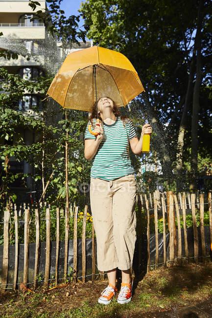 Молода смішна жінка з парасолькою та лімонадою в саду. — стокове фото