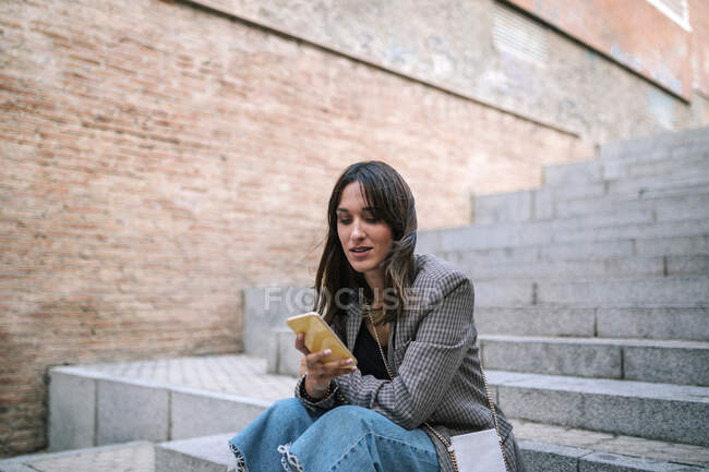 Woman using mobile phone while sitting on staircase — Stock Photo