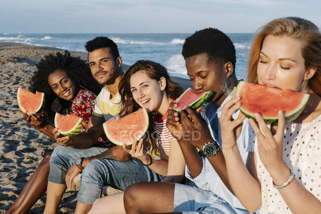 Friends eating slice of watermelon while sitting on beach during sunny day — Stock Photo
