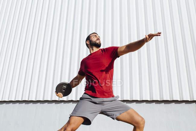 Молодой человек практикует метание диска, стоя у стены — стоковое фото