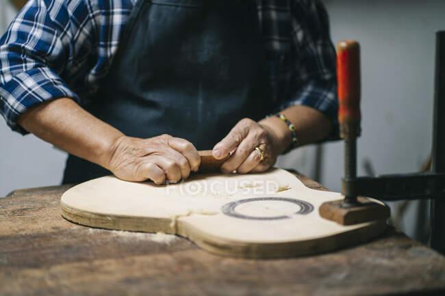 Gitarrenbauer schnitzt Gitarrenholz im Stehen in Werkstatt — Stockfoto