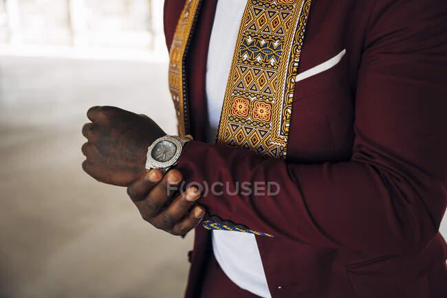 Jovem vestindo kente tradicional em terno enquanto está em pé na construção — Fotografia de Stock
