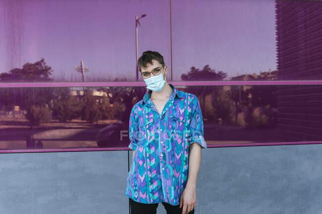 Небінарна людина в масці, стоячи проти рожевої скляної стіни. — стокове фото