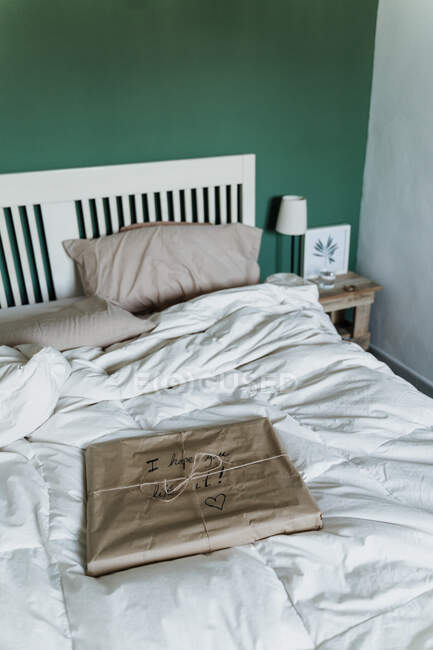 Gift wrapped in brown paper on bed at home — Fotografia de Stock