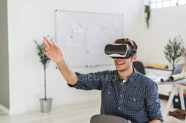 Smiling man sitting on chair while using visual reality simulator at office — Stock Photo