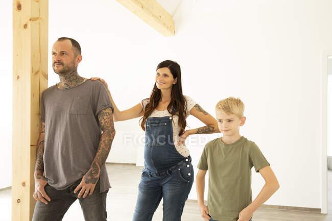 Родина відводить погляд, стоячи навпроти стіни в новому домі. — стокове фото