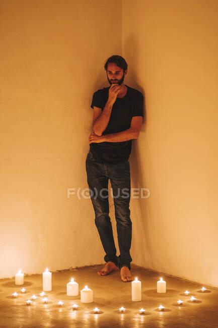 El hombre reflexivo de pie junto a velas encendidas contra la pared en el cuarto oscuro en casa - foto de stock
