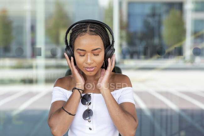 Young woman with headphone listening music while standing against glass wall in city - foto de stock