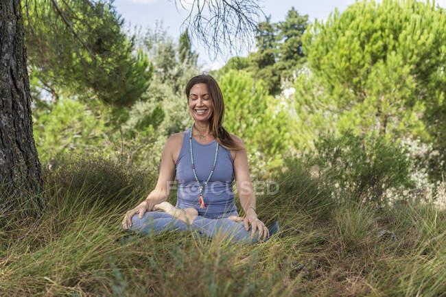 Mujer sonriente practicando yoga mientras está sentada bajo el árbol en la hierba - foto de stock
